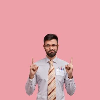 Pionowe ujęcie przystojnego niezadowolonego mężczyzny z grubym włosiem z oboma palcami wskazującymi w pustej przestrzeni, ubrany w formalne ubrania