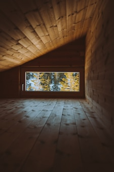 Pionowe ujęcie przytulnego strychu z oknem z widokiem na pokryty śniegiem las w norwegii