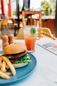 Pionowe ujęcie pysznego burgera i frytek oraz kieliszek koktajlu na stole