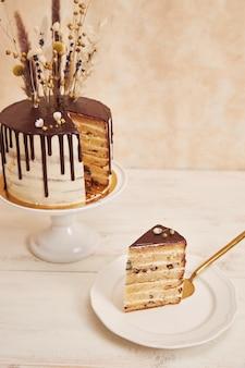 Pionowe ujęcie pysznego ciasta boho z czekoladową kroplą i kwiatami na wierzchu ze złotymi dekoracjami