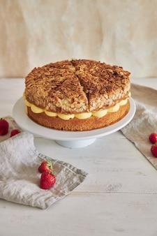 Pionowe ujęcie pysznego ciasta kremowego z chrupiącymi migdałami i truskawkami na stojaku na ciasto