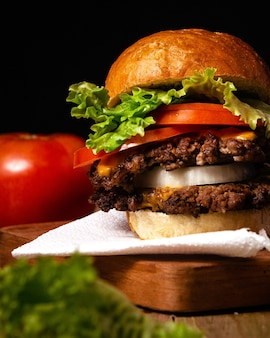 Pionowe ujęcie pysznego hamburgera na drewnianym talerzu z czarną ścianą