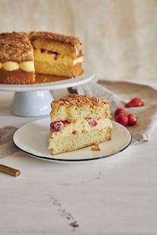 Pionowe ujęcie pysznego kawałka ciasta z kremem z chrupiącymi migdałami i truskawkami