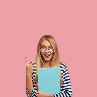 Pionowe ujęcie radosnej blondynki z pozytywnym wyrazem twarzy, wskazuje palcem wskazującym w górę, nosi niebieski podręcznik, pokazuje wolną przestrzeń