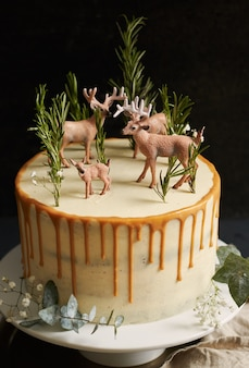 Pionowe ujęcie rozmarzonego ciasta z białą śmietaną i pomarańczową kroplówką z lasem i reniferami na górze