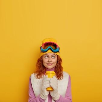 Pionowe ujęcie rozmarzonej, kontemplującej kobiety trzymającej gorący napój w jednorazowym kubku, marzącej o wspaniałych wakacjach zimą, na głowie nosi okulary narciarskie i czapkę, stoi pod dachem.
