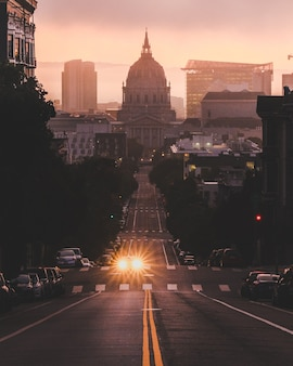 Pionowe ujęcie samochodów jadących drogą pośrodku budynków przy zachmurzonym niebie