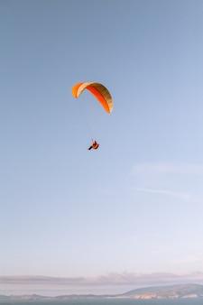 Pionowe ujęcie samotnej osoby ze spadochronem w dół pod pięknym niebieskim niebem