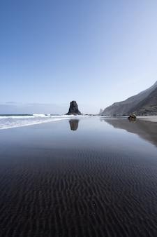 Pionowe ujęcie skalistego brzegu morza z naturalnymi śladami w przezroczystej wodzie