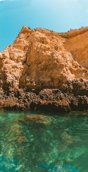 Pionowe ujęcie skalistego urwiska odbijającej się na morzu w słoneczny dzień