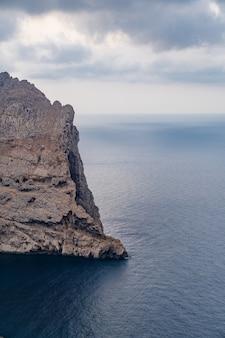 Pionowe ujęcie skalistych klifów nad morzem śródziemnym na majorce uchwycone w hiszpanii