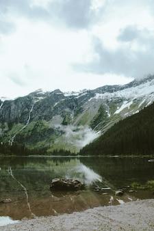 Pionowe ujęcie skały w jeziorze lawinowym, z zalesioną górą