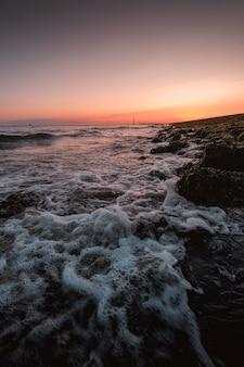 Pionowe ujęcie spienionych fal morza dochodzących do brzegu z niesamowitym zachodem słońca