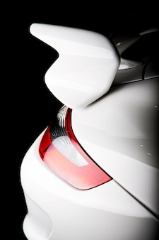 Pionowe ujęcie spoilera na białym luksusowym samochodzie pod światłami na białym tle