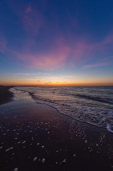 Pionowe ujęcie spokojnego oceanu podczas zachodu słońca w vrouwenpolder, zeeland, holandia