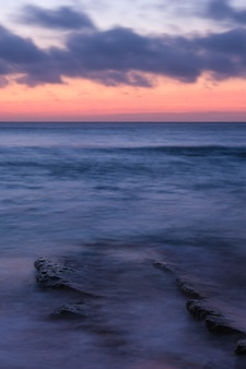 Pionowe ujęcie spokojnego oceanu z małymi falami i pomarańczowym pochmurnym niebem