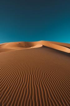 Pionowe ujęcie spokojnej pustyni pod czystym, błękitnym niebem uchwycone w maroku