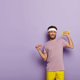 Pionowe ujęcie sportowego mężczyzny ubranego w odzież aktywną, trenuje mięśnie z hantlami, ma regularny trening na siłowni