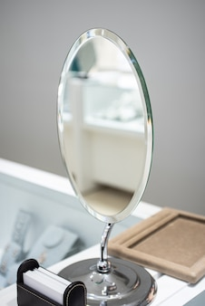 Pionowe ujęcie srebrnego lustra na komodzie