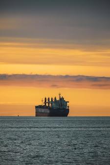 Pionowe ujęcie starego statku w jeziorze pod kolorowe niebo podczas zachodu słońca