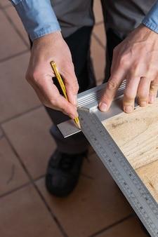 Pionowe ujęcie stolarza w trakcie wykonywania drewnianego stołu