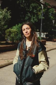 Pionowe ujęcie stylowej kobiety stojącej na zewnątrz