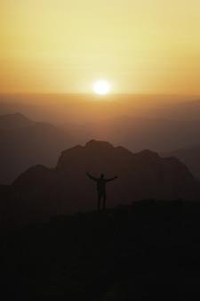 Pionowe ujęcie sylwetki męskiego turysty na szczycie góry patrzącego na zachód słońca