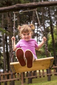 Pionowe ujęcie szczęśliwego dziecka płci żeńskiej kołyszącej się za drzewami