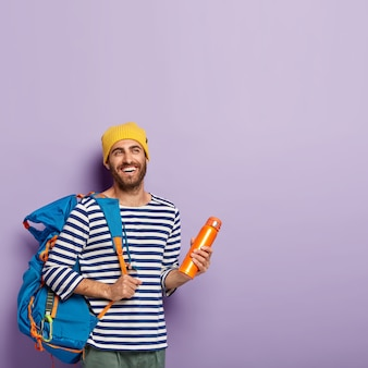 Pionowe ujęcie szczęśliwego nieogolonego turysty męskiego nosi duży plecak turystyczny, trzyma kolbę, odizolowane na fioletowej ścianie, wolna przestrzeń. ludzie i turystyka