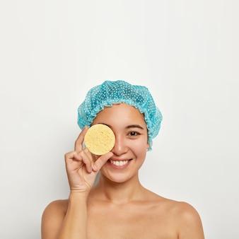 Pionowe ujęcie szczęśliwej młodej kobiety trzyma gąbkę na oku, wykonuje zabiegi kosmetyczne, usuwa makijaż przed wzięciem prysznica