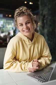 Pionowe ujęcie szczęśliwej uśmiechniętej kobiety siedzącej w kawiarni z laptopem.