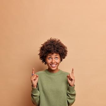 Pionowe ujęcie szczęśliwych radosnych modelek powyżej z szerokim uśmiechem z przyjemnością pokazuje miejsce na kopię dla treści reklamowych nosi zwykły sweter odizolowany na beżowej ścianie