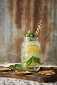Pionowe ujęcie szklanego napoju mojito z liśćmi mięty i plasterkami cytryny na drewnianym napoju