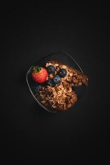 Pionowe ujęcie szklanej miski zdrowej przekąski z jagodami, truskawka na czarnym stole