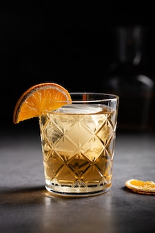 Pionowe ujęcie szklanki whisky ozdobionej plasterkiem suszonej pomarańczy