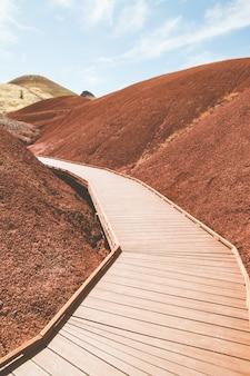 Pionowe ujęcie sztucznej drewnianej drogi na wzgórzach z czerwonego piasku