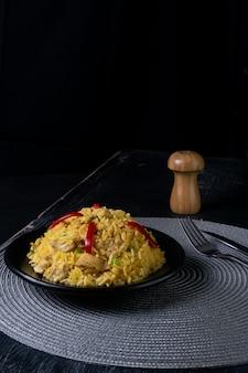 Pionowe ujęcie talerza pysznego ugotowanego ryżu z przyprawami i kurczakiem na stole