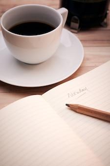 """Pionowe ujęcie tekstu """"poniedziałek"""" zapisanego w zeszycie z białą filiżanką kawy z boku"""