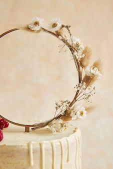Pionowe ujęcie tortu weselnego ozdobionego świeżymi owocami i jagodami oraz pierścionkiem z kwiatów