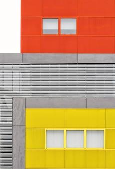 Pionowe ujęcie unikalnego nowoczesnego budynku z kreatywnymi zwrotami architektury