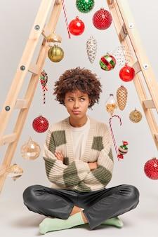 Pionowe ujęcie urażonej niezadowolonej kobiety siedzącej ze skrzyżowanymi nogami na podłodze ma niezadowolony wyraz twarzy i zamierza udekorować dom pozami bombkami noworocznymi