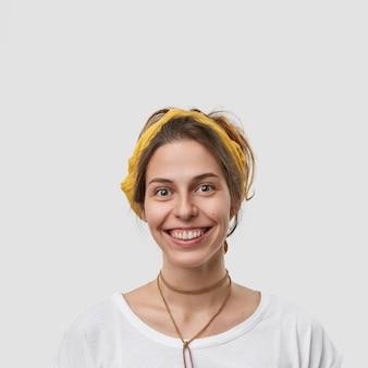 Pionowe ujęcie uroczej, przyjemnie wyglądającej kobiety z wesołym wyrazem twarzy, wygląda bezpośrednio szczęśliwie