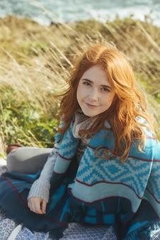 Pionowe ujęcie uśmiechniętej kobiety siedzącej na brzegu morza