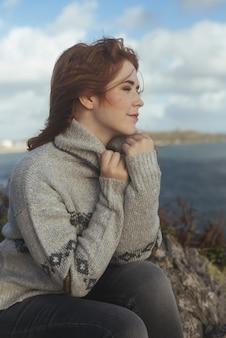 Pionowe ujęcie uśmiechniętej kobiety z morzem