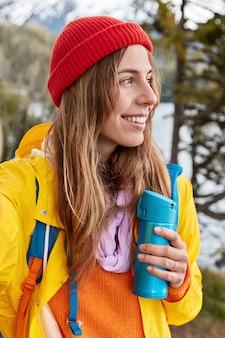 Pionowe ujęcie uśmiechniętej podróżniczki w czerwonym kapeluszu, żółtym płaszczu, rozciąga rękę, robi selfie nierozpoznawalnym urządzeniem