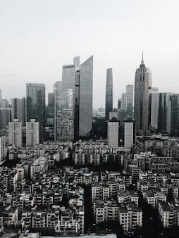 Pionowe ujęcie w skali szarości obszaru miejskiego z wieloma wieżowcami o różnych kształtach
