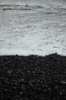 Pionowe ujęcie w skali szarości przedstawiające fale na plaży zbliżające się do brzegu