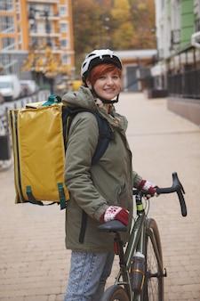 Pionowe ujęcie wesołej młodej kobiety pracującej na swoim rowerze jako kurier dostawy