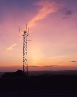 Pionowe ujęcie wieży telekomunikacyjnej na polu pod zapierającym dech w piersiach niebem - idealne na tapetę