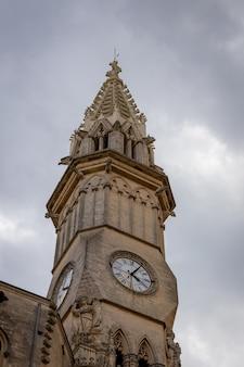 Pionowe ujęcie wieży zegarowej katedry w manacor na majorce w hiszpanii
